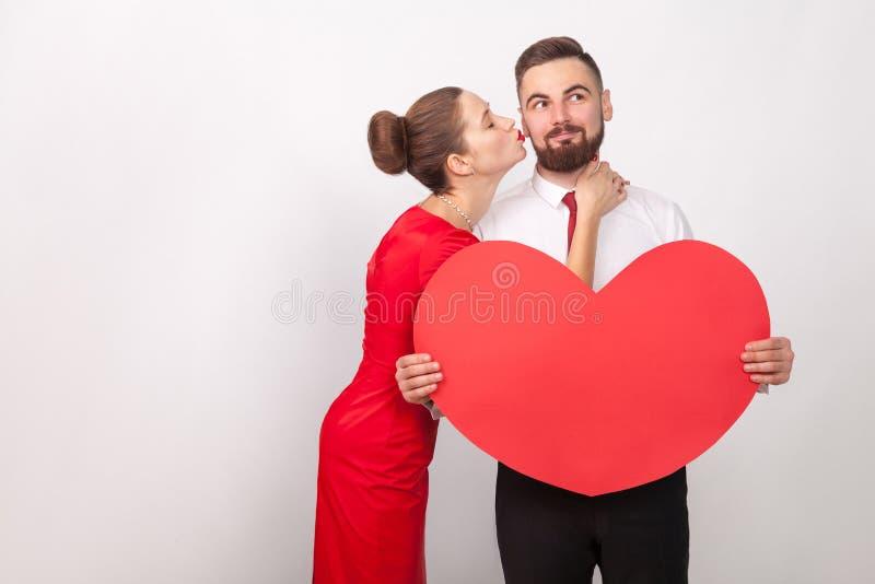 Bemannen Sie Wunsch etwas und lächeln, perfekte Frau, küssen ihn an der Backe lizenzfreie stockbilder