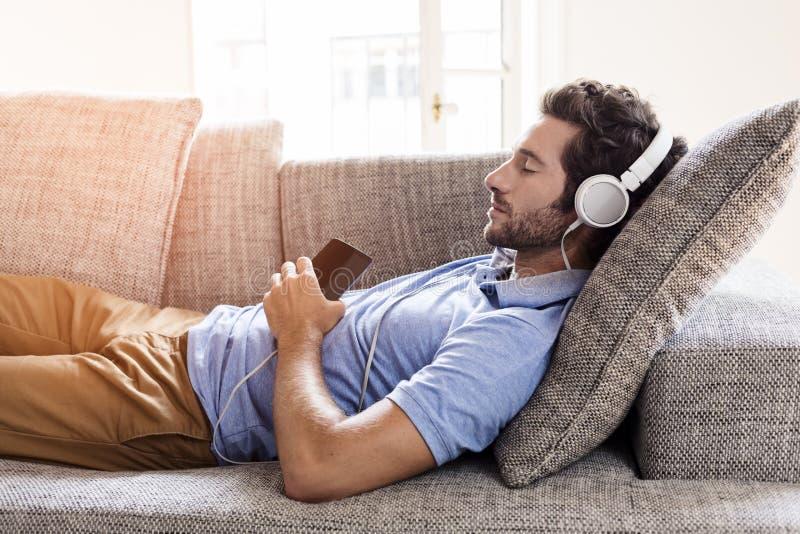 Bemannen Sie zu Hause auf hörenden Sofa dem Musik mit einem Smartphone stockfotos
