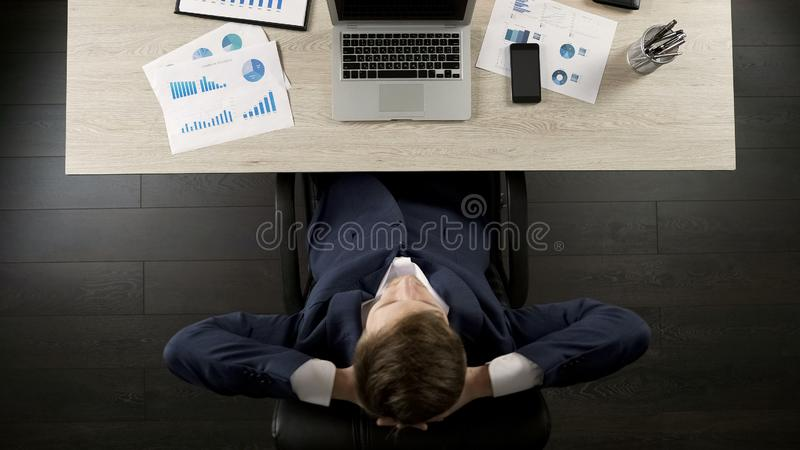 Bemannen Sie zurück sitzen im Bürostuhl, der mit Geschäftsprojekt entspannt wird und zufrieden gestellt ist stockbild