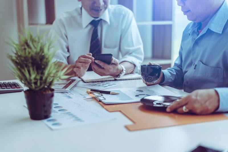Bemanning die van midden-leeftijds de Aziatische twee bedrijfsleiders met nieuw startproject werken terwijl het zitten royalty-vrije stock afbeelding