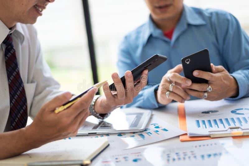 Bemanning die van midden-leeftijds de Aziatische twee bedrijfsleiders met nieuw startproject werken terwijl het zitten stock afbeelding