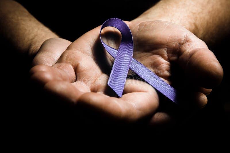 Bemannt die Hände, die purpurrotes Bewusstseinsband der häuslichen Gewalt halten stockbild