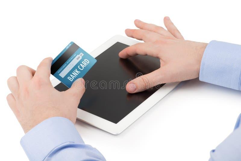 Bemannt die Hand, die eine Kreditkarte über einem Tablettenbaut. hält stockfotografie
