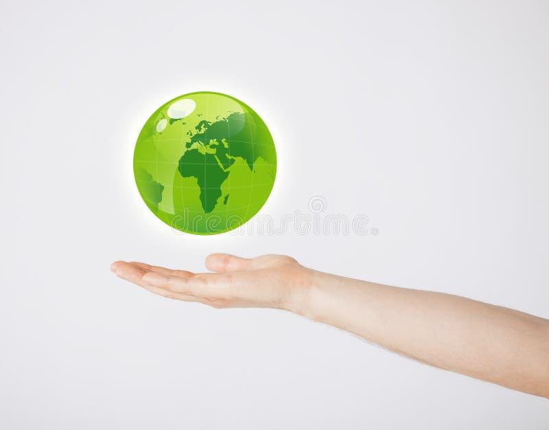 Bemannt die Hand, die grüne Kugel hält lizenzfreie stockfotografie