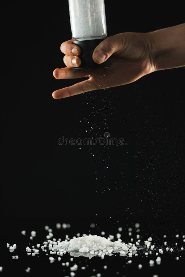 Bemannt die Hand, die Seesalz gegen schwarzen Hintergrund besprüht stockbilder