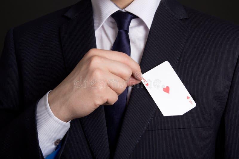 Bemannt Handversteckende Spielkarte in der Klagentasche lizenzfreie stockfotografie
