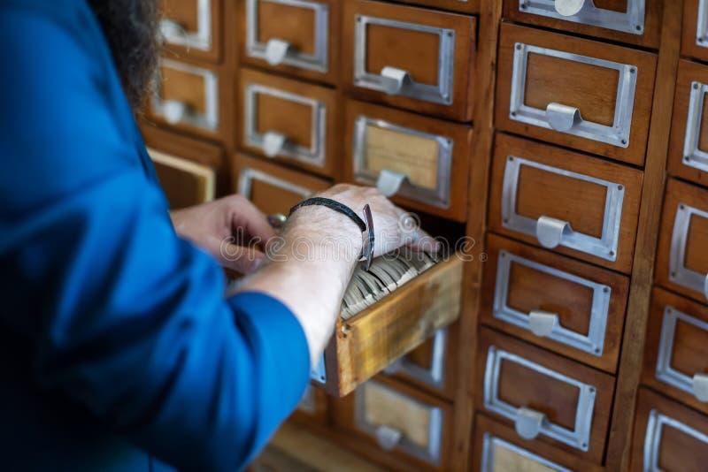 Bemant hand die naar dossiers in bibliotheek of archief zoeken stock afbeelding
