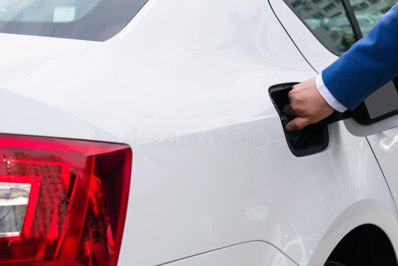Bemant hand opent het tankdeksel met benzine van de auto royalty-vrije stock foto's