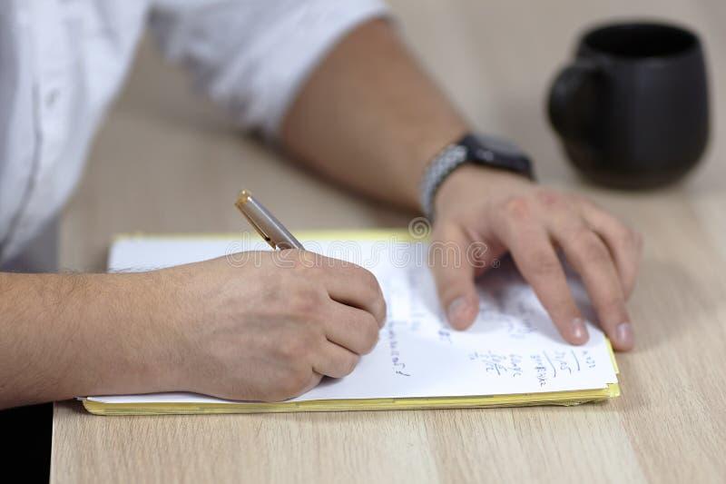 Bemant handen op witte uitrusting schrijft met rolpen op het document op houten lijst wat Latijn, of geneeskundetermijnen De kop  stock fotografie