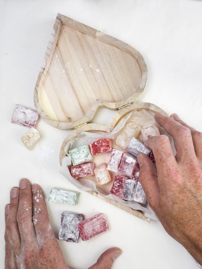 Bemant handen plaatsend Turkse verrukking in een hart gevormde doos stock foto's