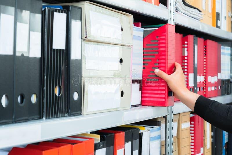 Bemant het met de hand plukken van een lege blinde omslag met dossiers van de plank Archivistisch, stapels documenten op het kant royalty-vrije stock afbeeldingen