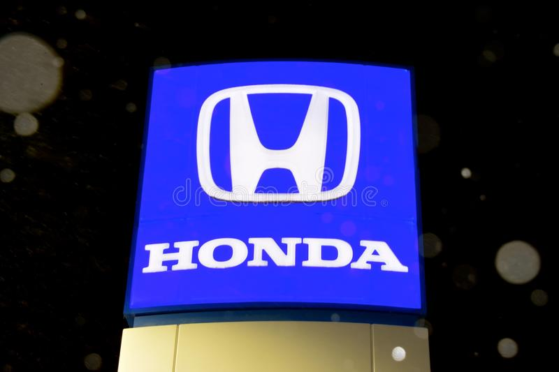 Snow is falling on the Honda Logo sign royalty free stock photos