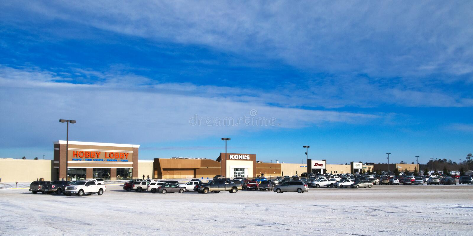 BEMIDJI, MN - 24 DEC 2018: Paul Bunyan Mall and parking lot in winter. Partially blue skies and vehicles are seen stock photos