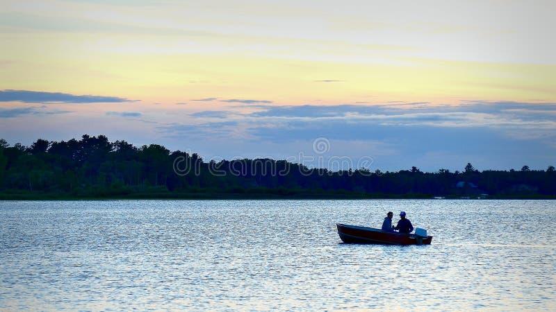 BEMIDJI MN - 10 JULI 2016: Kontur av par som fiskar i ett fartyg på en sjö i Minnesota royaltyfri bild