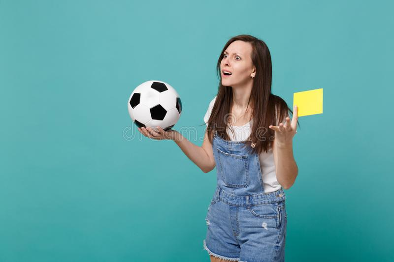 Bemused puzzled woman football fan support team with soccer ball, yellow card, propose player retire from field isolated. On blue turquoise background. People stock photo