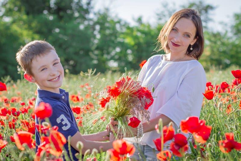 Bemuttern Sie Brunette im Weiß mit Sohn zusammen auf blühendem rotem Mohnblumenfeld stockbild