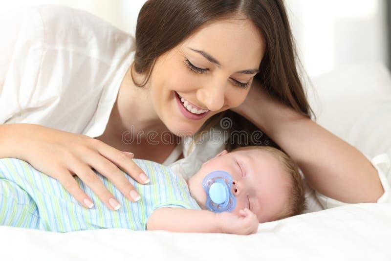 Bemuttern Sie das Aufpassen ihres Babys, auf einem Bett zu schlafen stockfotografie