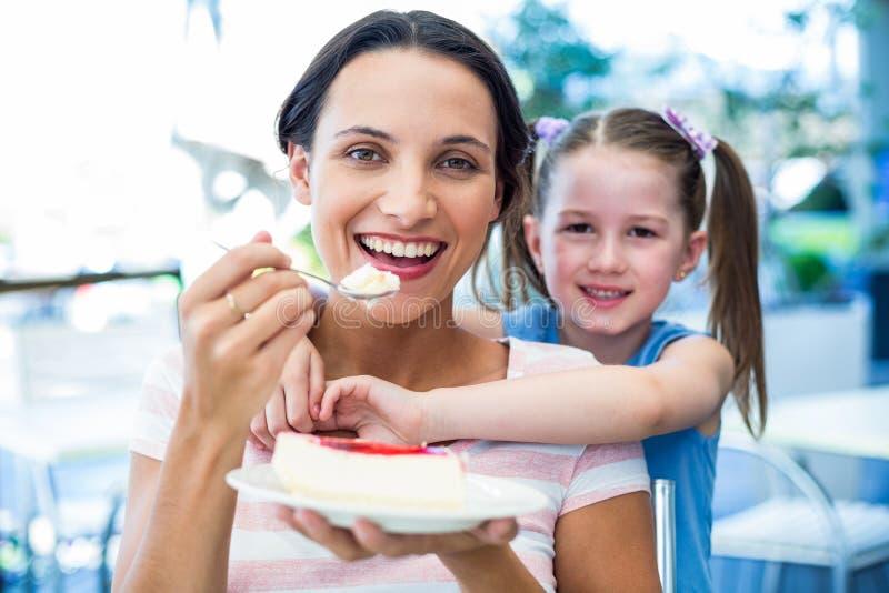 Bemuttern Sie das Essen eines Stückes des Kuchens mit ihrer Tochter lizenzfreie stockfotografie