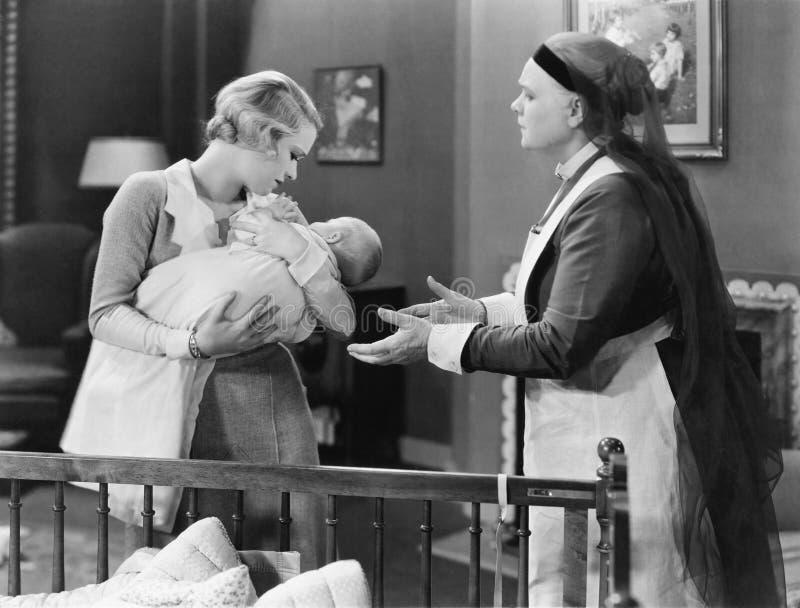 Bemuttern Sie das Geben einem Kindermädchen ihres schlafenden Babys (alle dargestellten Personen sind nicht längeres lebendes und stockfoto