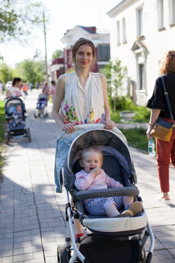 Bemuttern Sie das Gehen in die Straße mit ihrem Baby im Spaziergänger stockfoto