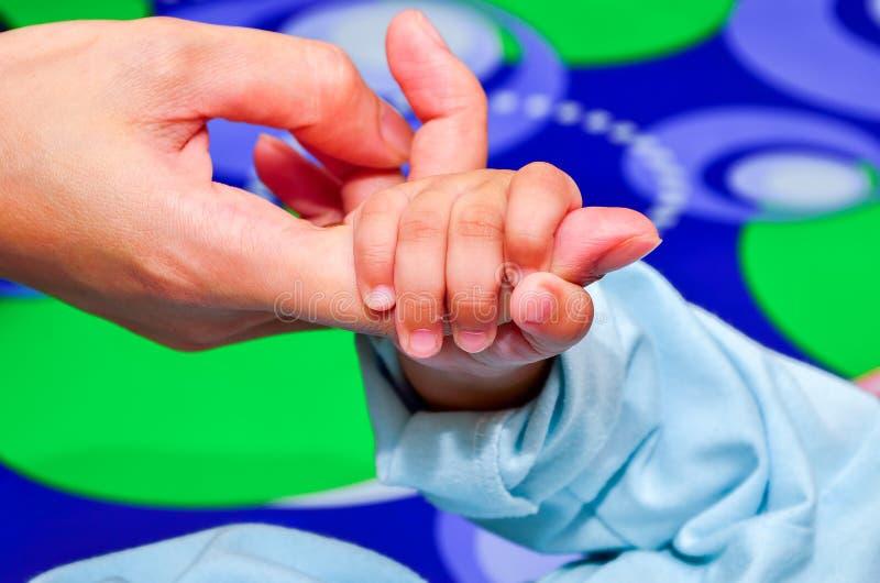 Bemuttern Sie das Halten der Hand seines neugeborenen Sohns lizenzfreies stockbild