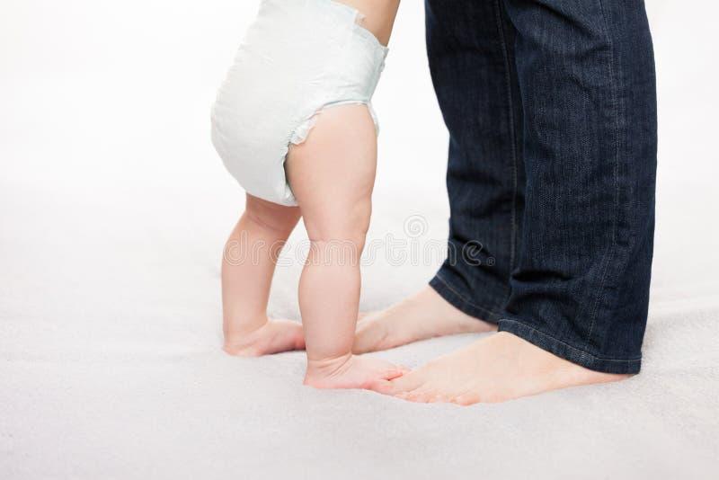 Bemuttern Sie das Halten des kleinen Babykinderjungen, der ersten Schritt macht stockfotos
