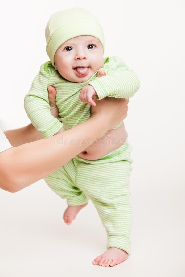Bemuttern Sie das Halten des kleinen Babykinderjungen, der ersten Schritt macht stockfotografie