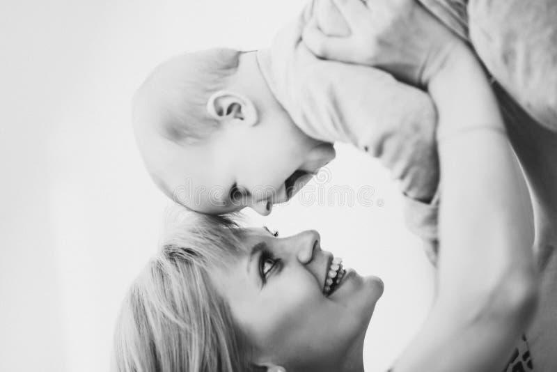 Bemuttern Sie das Halten ihres Babys hoch und das Toching durch Nasen lizenzfreie stockfotos