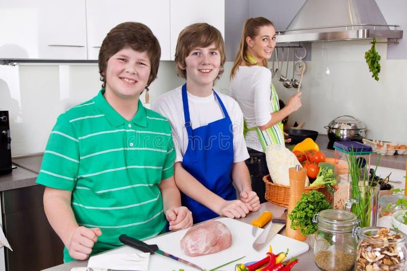 Bemuttern Sie das Kochen mit ihren Söhnen in der Küche - Familienleben. stockbilder