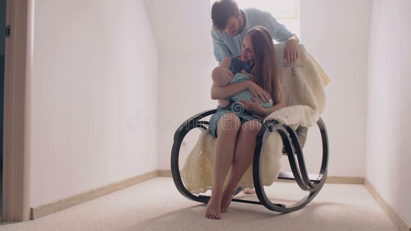 Bemuttern Sie das Lächeln am neugeborenen Sohn, der ihn in einem Schaukelstuhl einschläfert Vater kommt zu ihnen 4K lizenzfreie stockfotografie