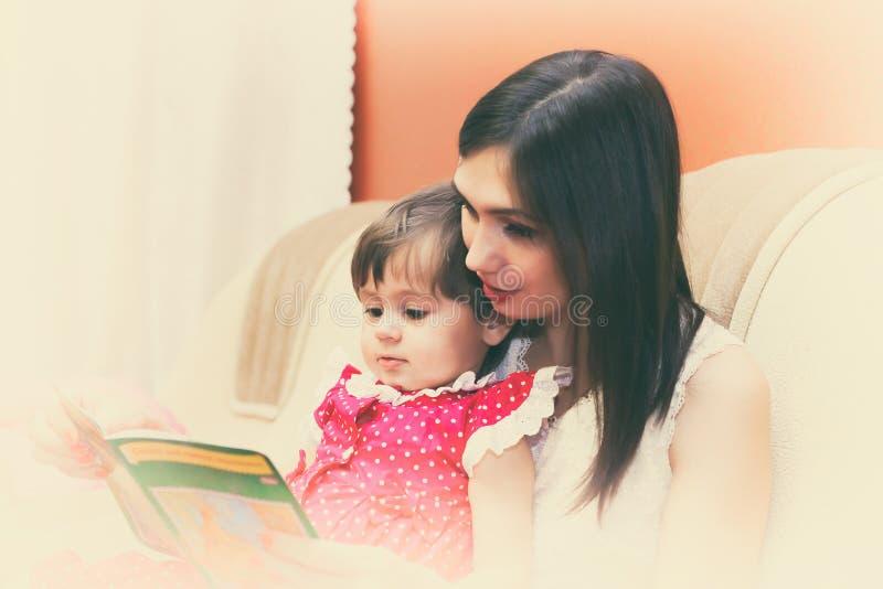 Bemuttern Sie das Lesen eines Buches mit ihrer kleinen Tochter stockbild