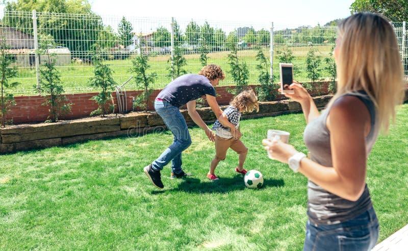 Bemuttern Sie das Machen des Fotos ihres Ehemann- und Sohnspielens stockbild