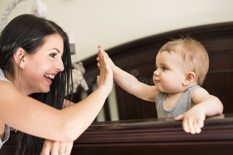 Bemuttern Sie das Setzen des Babys, um an der Krippe zu schlafen stockbilder