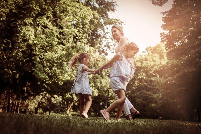 Bemuttern Sie das Spielen auf Wiese mit ihrer kleinen Tochter zwei lizenzfreie stockbilder