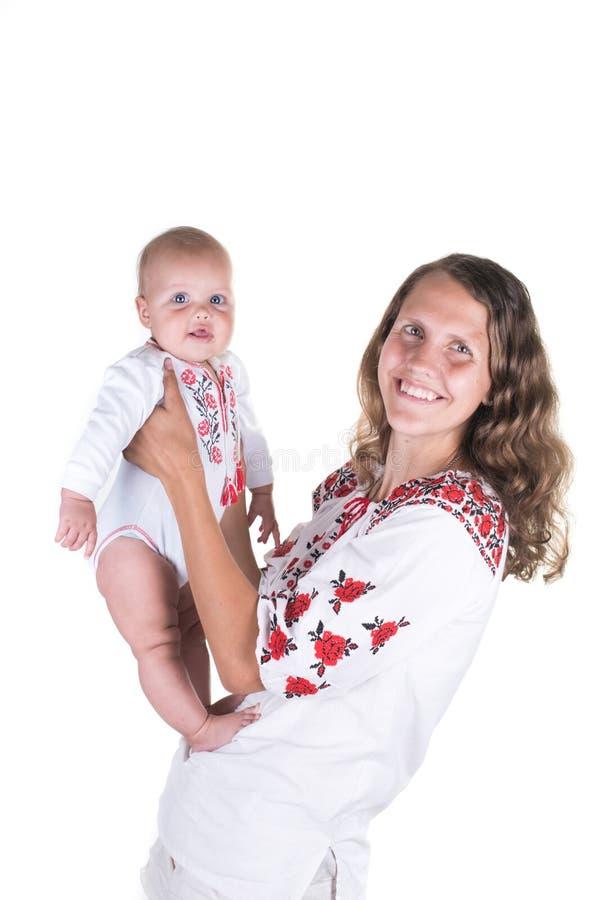 Bemuttern Sie das Spielen mit Baby, der glücklichen Familie, die den Spaß haben, der Innen ist, der Mutter und Kind, die auf weiß lizenzfreie stockfotografie