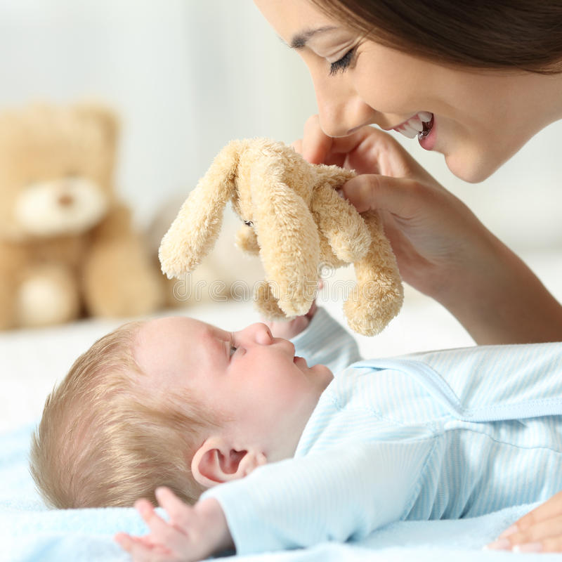 Bemuttern Sie das Spielen mit ihrem Baby mit einem Teddybären lizenzfreies stockbild