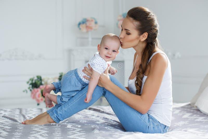 Bemuttern Sie das Spielen mit ihrem neugeborenen Sohn, der auf Bett liegt lizenzfreies stockbild