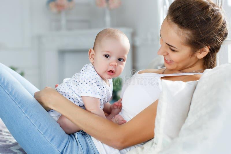 Bemuttern Sie das Spielen mit ihrem neugeborenen Sohn, der auf Bett liegt lizenzfreie stockfotografie