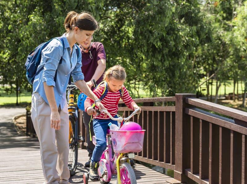 Bemuttern Sie das Unterrichten ihrer Tochter, ein Fahrrad zu reiten stockfotografie