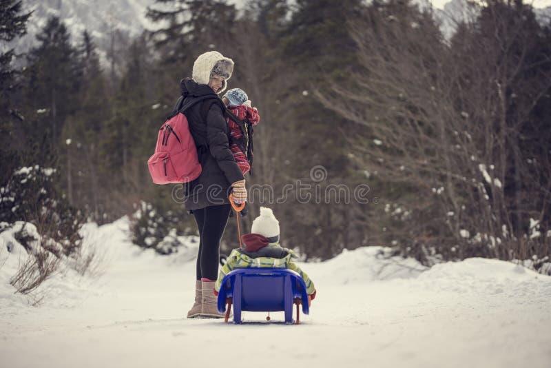 Bemuttern Sie das Ziehen ihres Kindes durch Winterschnee auf einem Schlitten lizenzfreie stockfotos