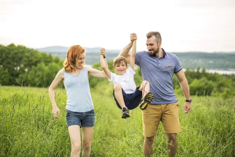 Bemuttern Sie den Vater und Tochter, die an der grünen Wiese spielen lizenzfreies stockfoto