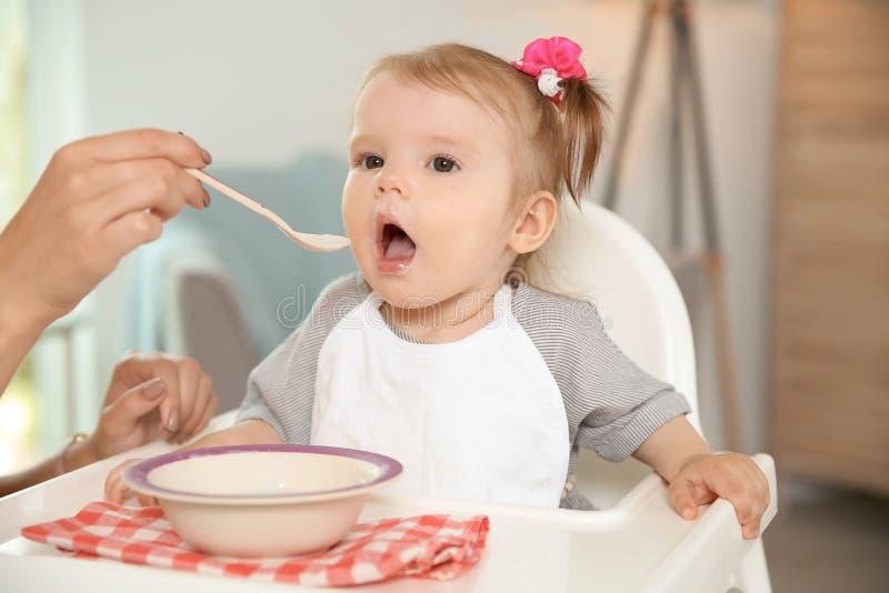 Bemuttern Sie die Fütterung ihres netten kleinen Babys mit gesundem Lebensmittelhaus lizenzfreies stockbild