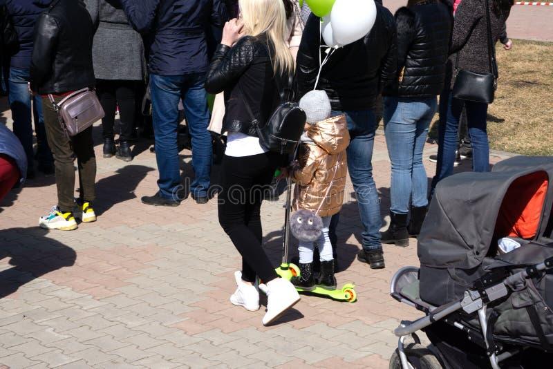 Bemuttern Sie die Tochter- und Sohnfamilie im Park gehend mit Ball- und Rochenroller lizenzfreies stockfoto