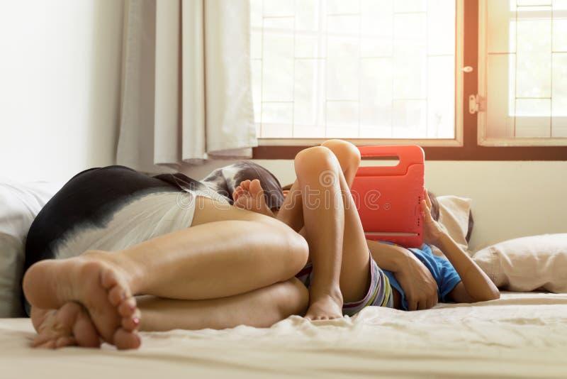 Bemuttern Sie die Umarmung ihres Sohns im Bett während seine spielende Tablette stockfotos