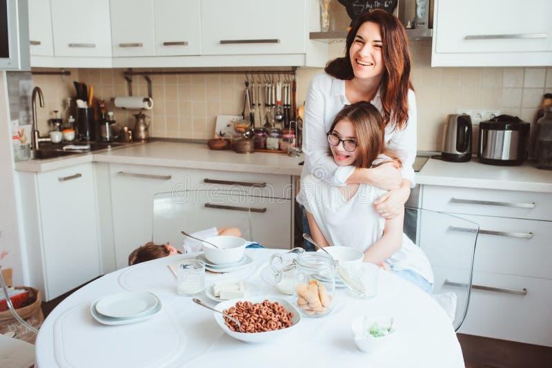 Bemuttern Sie Frühstücken mit jugendlich Tochter zu Hause in der modernen weißen Küche lizenzfreies stockbild