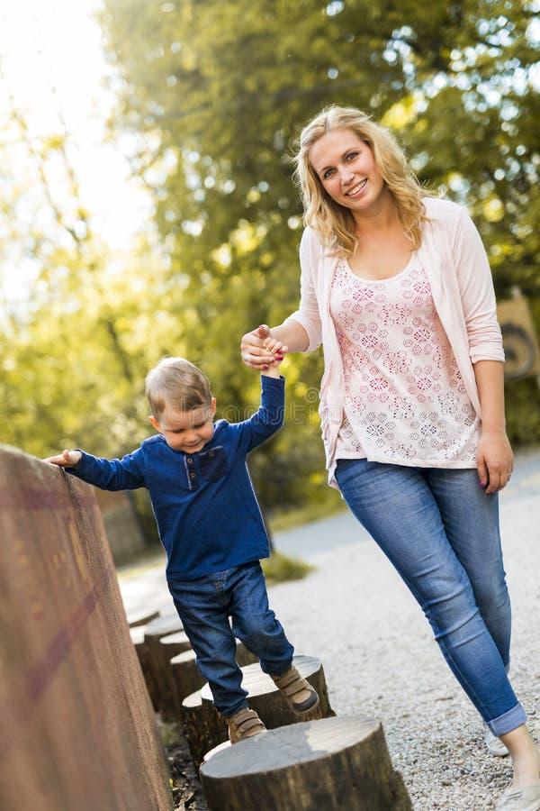 Bemuttern Sie Händchenhalten mit ihrem Sohn und dem Helfen er zu gehen stockfotografie
