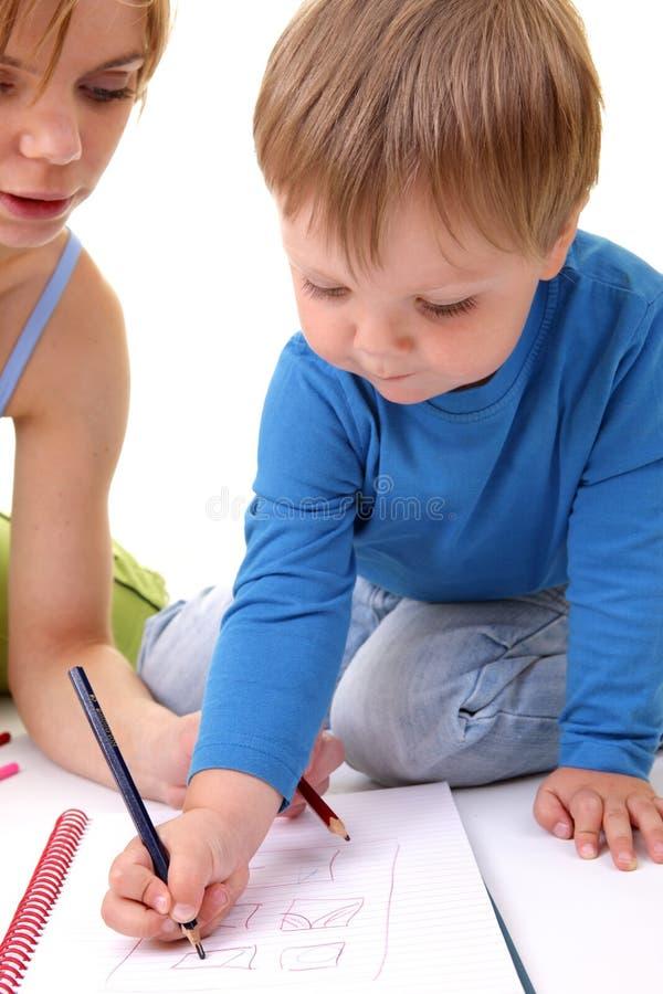 Bemuttern Sie helfen ihrem Sohn mit Zeichnung. lizenzfreies stockfoto