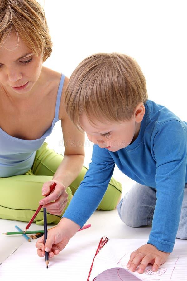 Bemuttern Sie helfen ihrem Sohn mit Zeichnung. stockfotografie