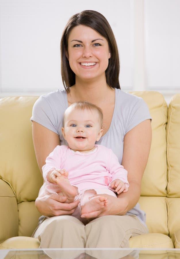 Bemuttern Sie Holdingschätzchen auf Sofa zu Hause lizenzfreie stockfotografie