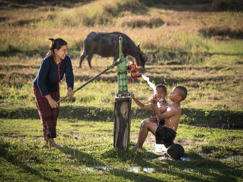 Bemuttern Sie ihre Sohndusche, die von der Grundwasserpumpe im Freien ist lizenzfreie stockfotografie